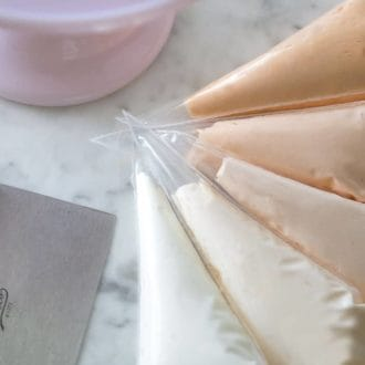 piping bags of Italian buttercream colored in an ombré of pastel orange.