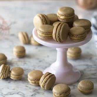 Pumpkin macarons piled on a cake plate with others scattered around it.