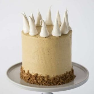 A photo of a Pumpkin Pie Cake on a cake stand with large meringue dollops.