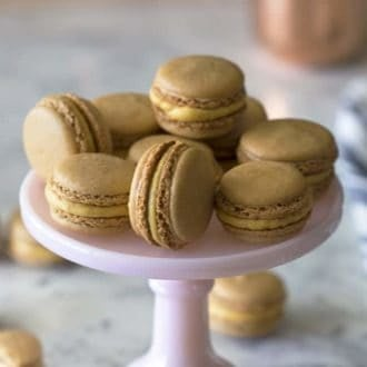 pumpkin macarons on a pink tray