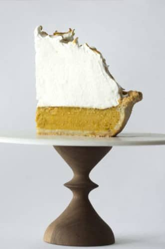 A side view of a single slice of pumpkin meringue pie on a cake plate