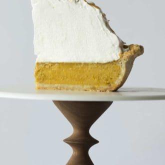 piece of pumpkin meringue pie on a cake stand