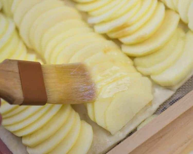 An apple tart getting brushed with butter