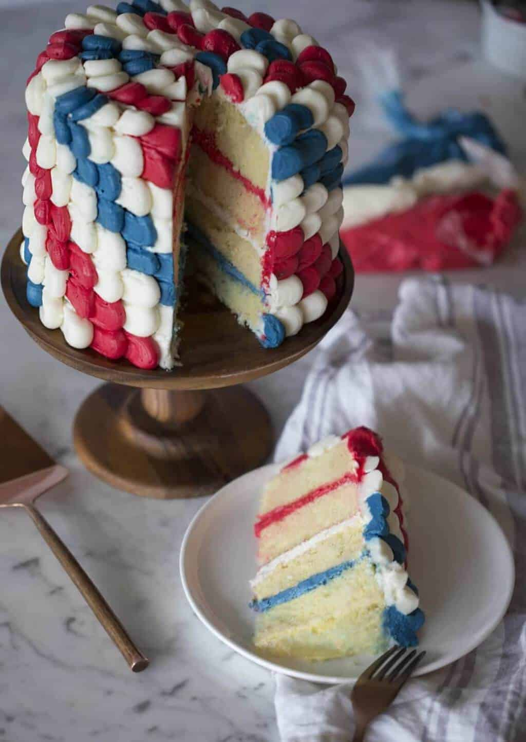 A photo of a red, white and blue cake on a cake stand.
