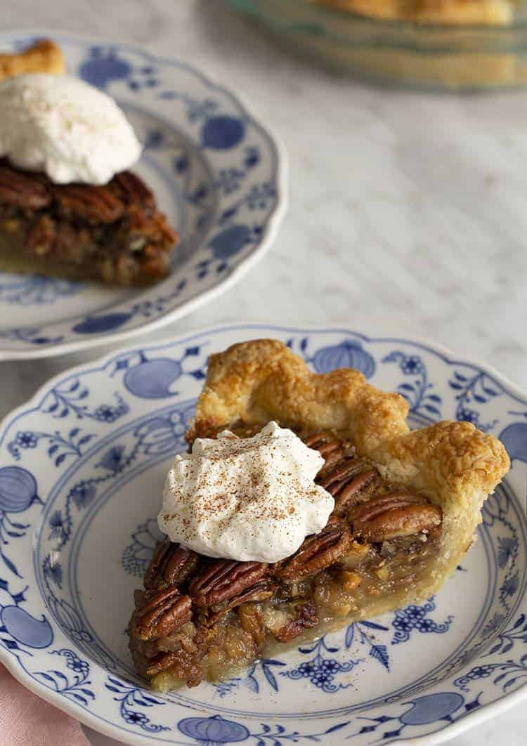 two pieces of pecan pie on blue and white plates on a marble table