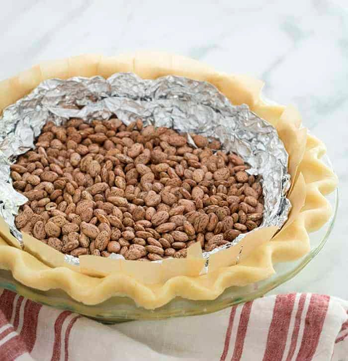 An unbaked pie crust filled with foil and beans