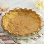 A perfectly golden pie crust on a white marble table