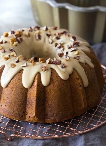 A pumpkin bundt cake on an oven rack with walnuts sprinkled around it.