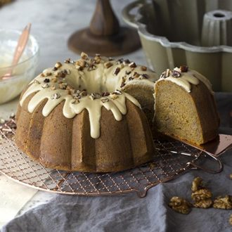 A pumpkin bundt cake on an oven rack with a piece being removed from it.