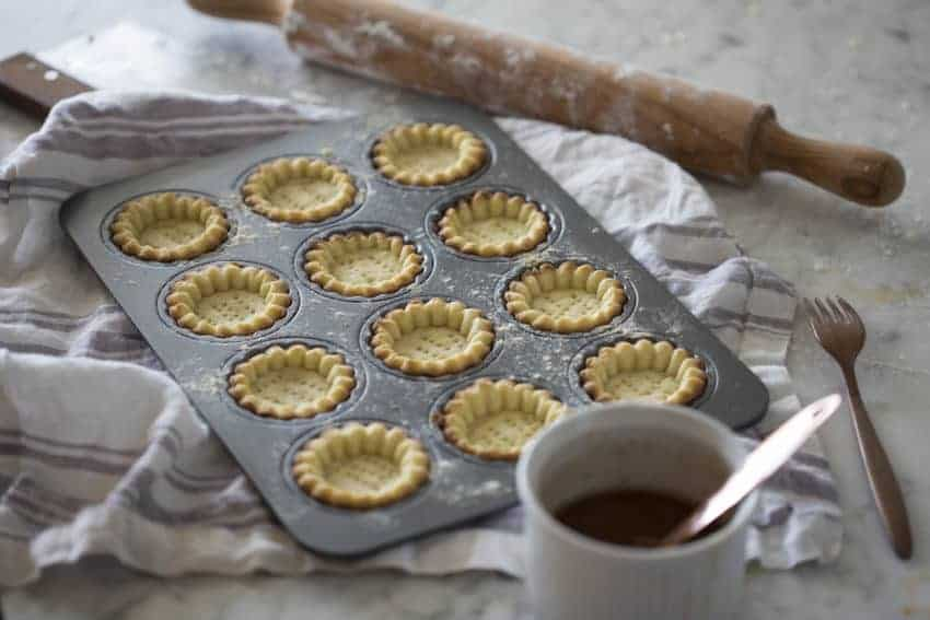 A photo of baked tart shells ready to be filled.