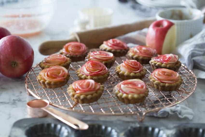 A photo of baked Rose Apple Tarts on a copper cooling rack.