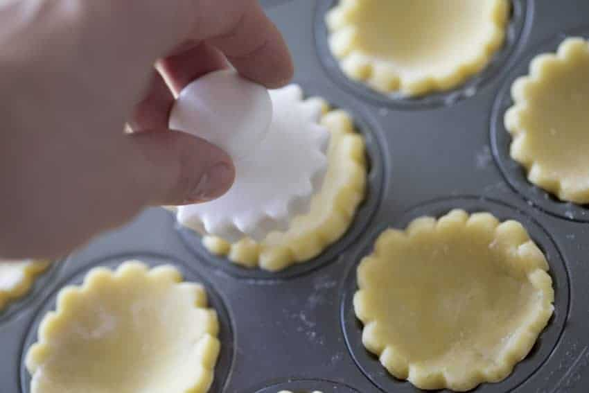 Plastic form pressing into pastry crust to push it down.