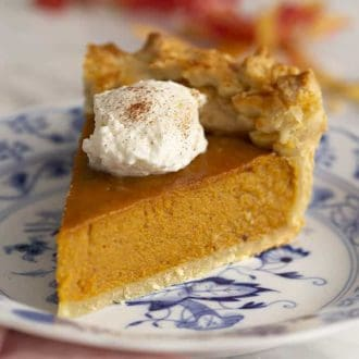 A piece of sweet potato pie topped with a dollop of whipped cream