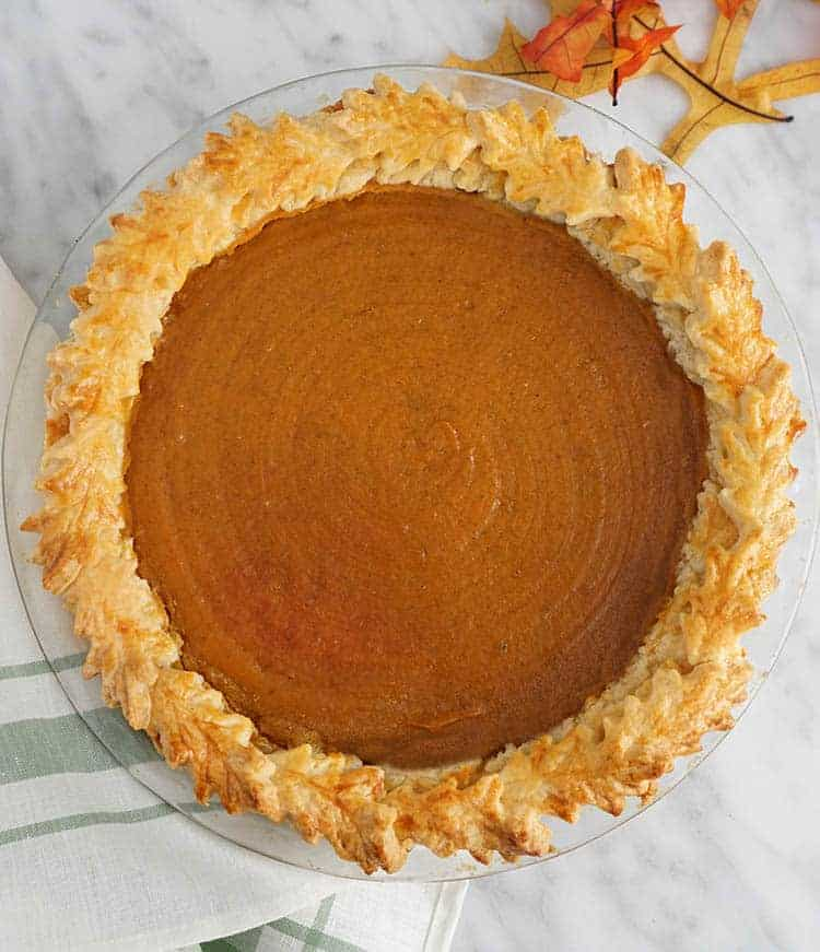 A top down shot of a sweet potato pie on a white marble table