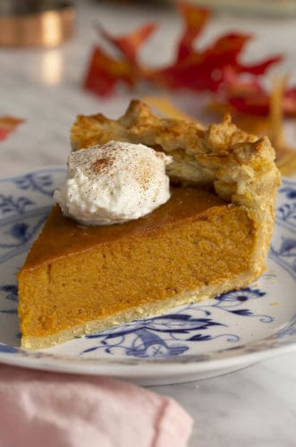 A piece of sweet potato pie on a blue and white plate