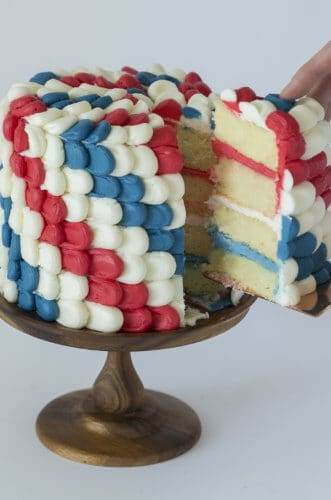 A photo of a Red, White & Blue Cake with a piece being removed.