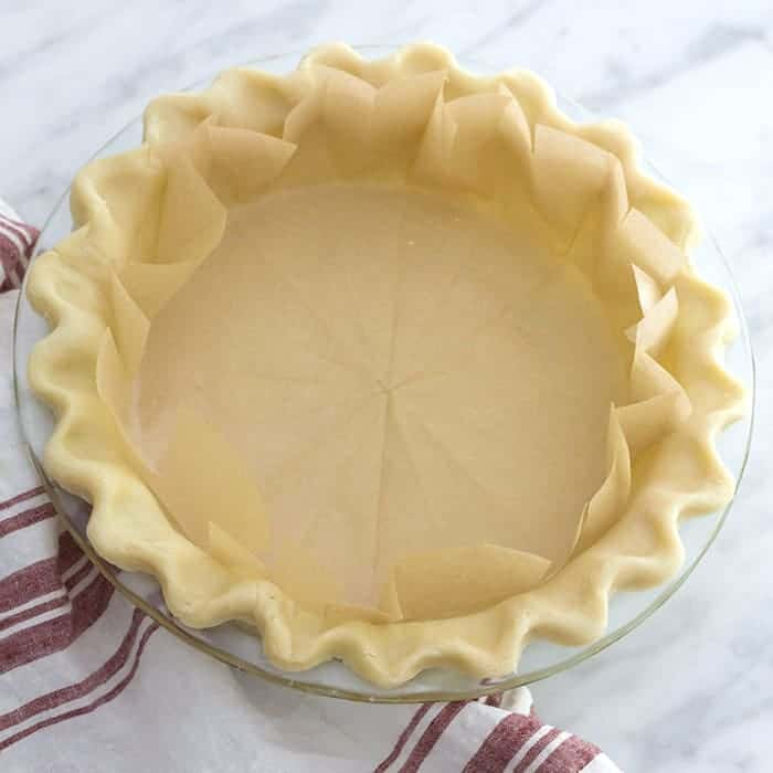 An unbaked pie crust with a parchment paper liner inside