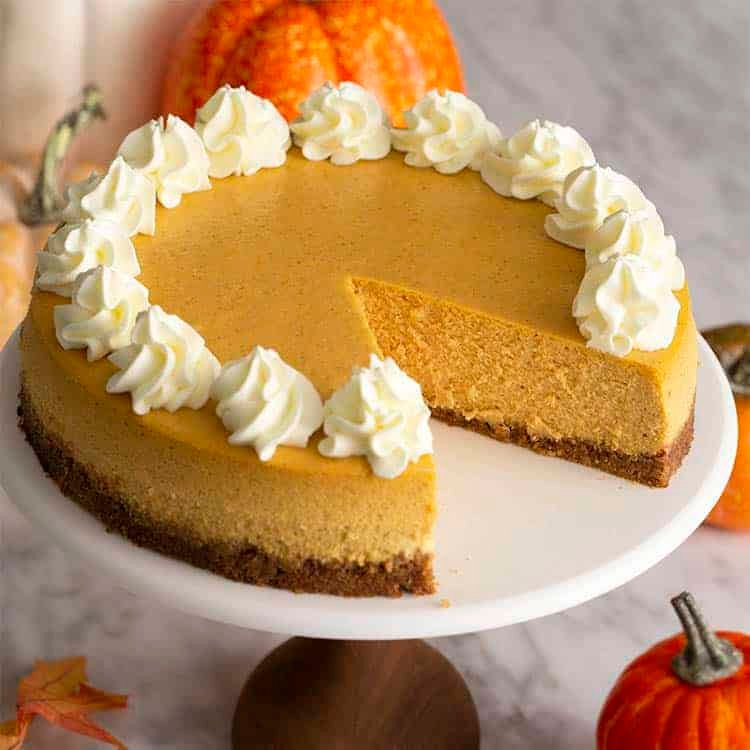 A pumpkin cheesecake on a cake stand with a piece removed