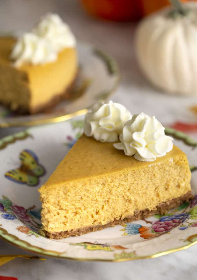 Tow pieces on pumpkin cheesecake topped with whipped cream on