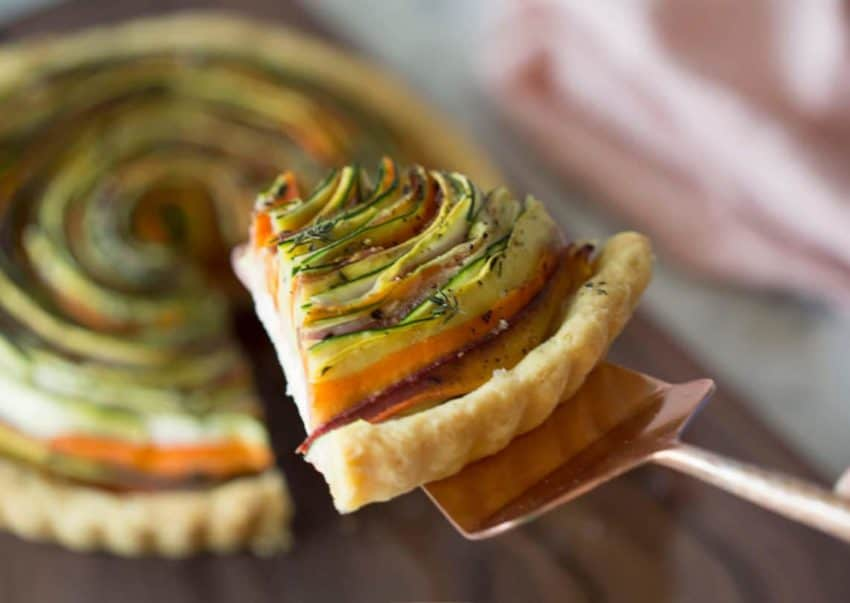 Photo of a spiral vegetable tart with a piece being removed