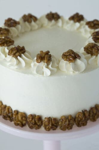A photo of a walnut maple cake, decorated with walnuts.