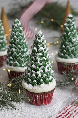 A photo of a group of Christmas tree cupcakes surrounded by evergreen branches