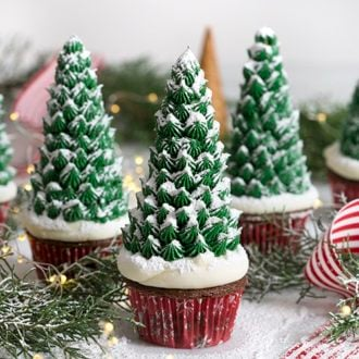 A photo of three Christmas tree cupcakes on a white marble table.