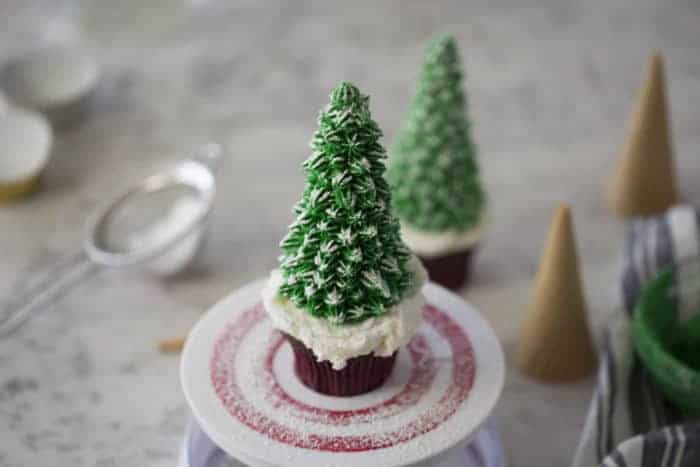 Christmas tree cupcakes dusted with powdered sugar to mimic snow.