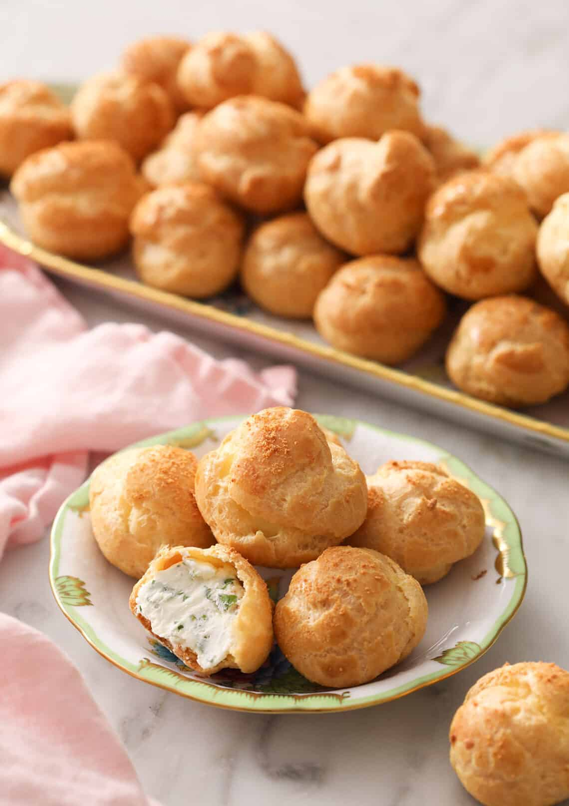 Cheese puffs on a small plate in front of a serving tray full of them
