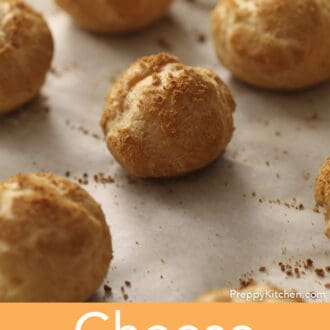 Some cheese puffs cooling on a baking sheet.