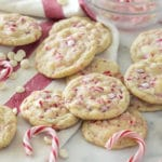 A photo of white chocolate peppermint cookies on a marble table surrounded by candy canes