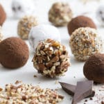 A photo of spherical brandies truffles on a white marble table.