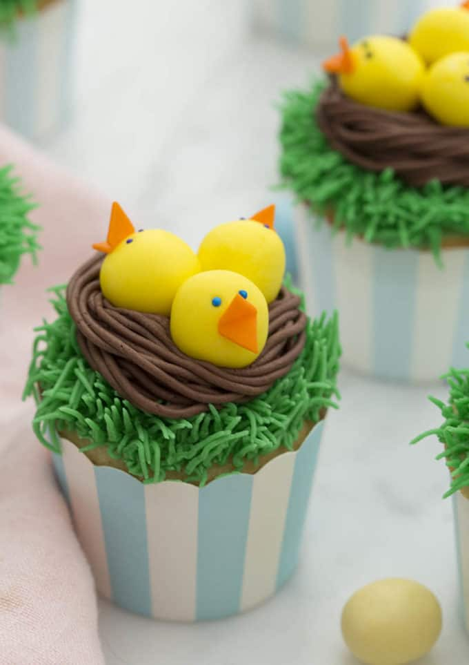 Easter Chick cupcakes on a white marble table.
