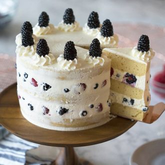 A photo showing a mascarpone berry cake on a wooden cake stand with a piece being removed