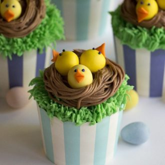 A photo showing cupcakes with baby chicks in a chocolate nest on top