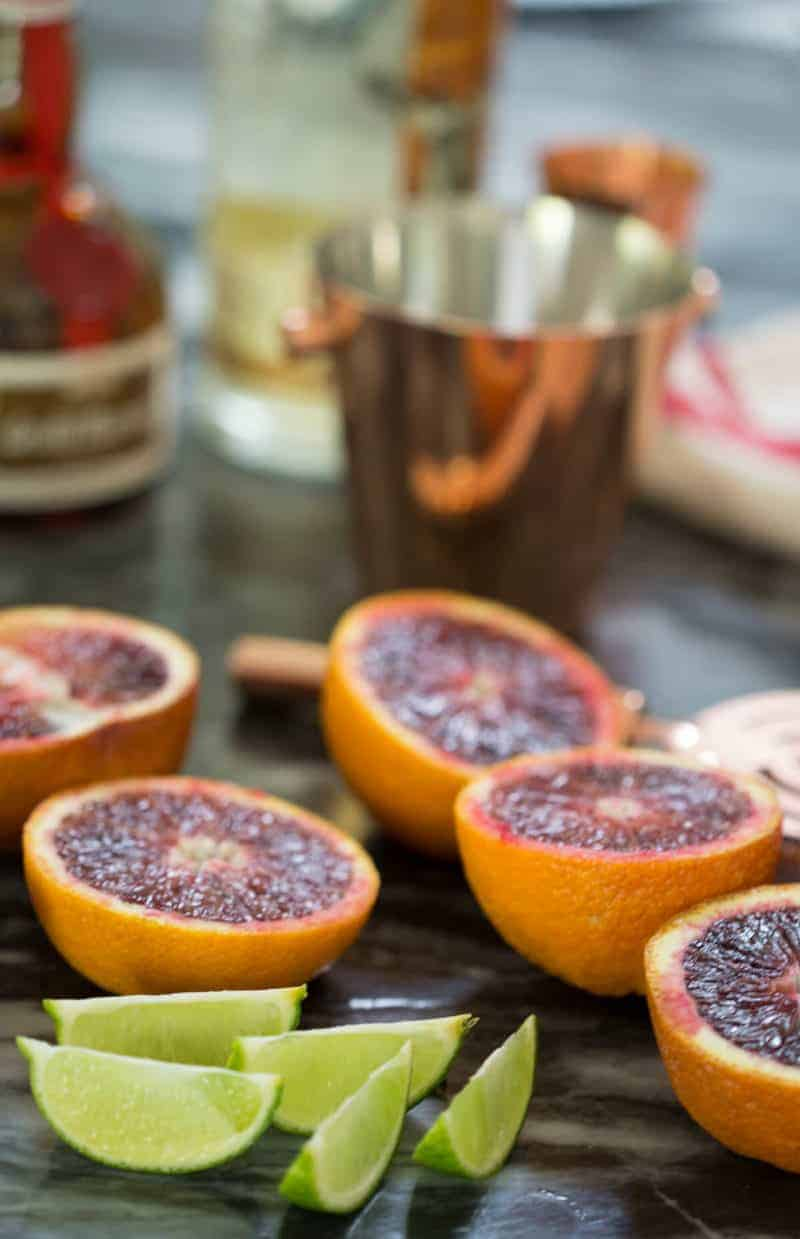 A photo of blood oranges and limes cut in half.