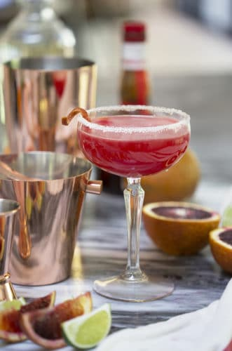 A photo of a Texas margarita in a coupe glass among copper bar tools.