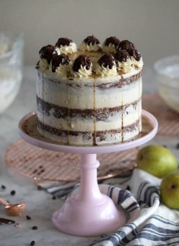 A photo of a chocolate pear cake on a soft pink cake stand
