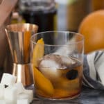 A photo of an old fashioned cocktail with the ingredients around it.