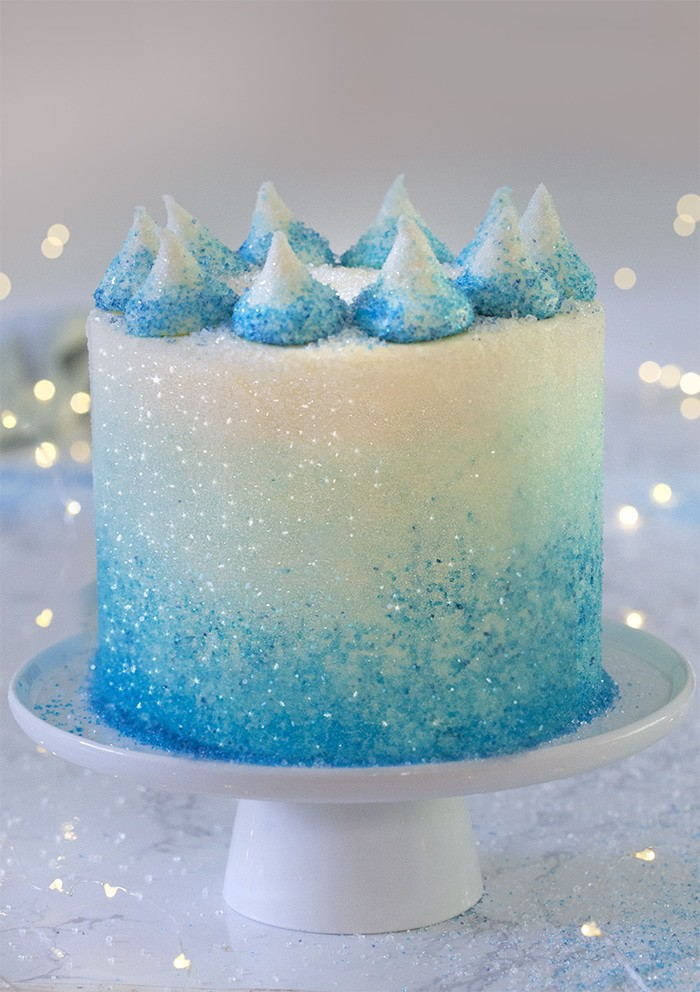 A photo of a blue ombre cake on a white cake stand surrounded by lights