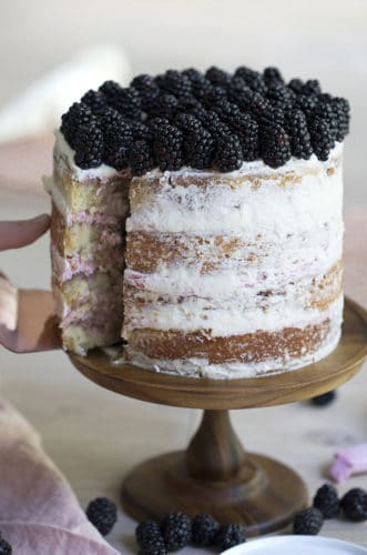 A photo of a blackberry cake complately covered with fresh blackberries on top.
