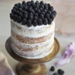 A 3/4 shot of a blackberry cake on a wooden cake stand with some berries in the background