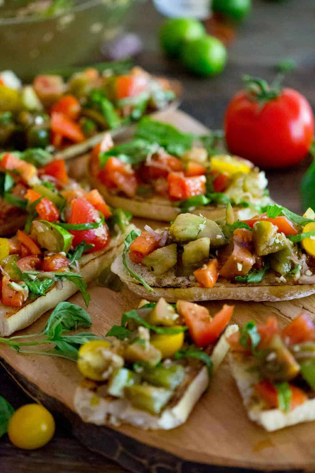 A photo of Heriloom Tomato Bruschetta on a wooden serving board.