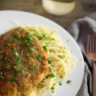 A photo of chicken piccata on a plate ready to be served.