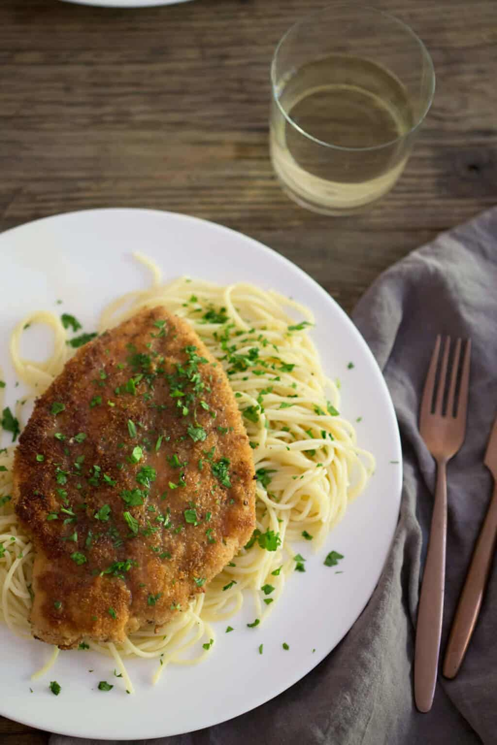 A photo of chicken piccata on a plate topped with fresh parsley.
