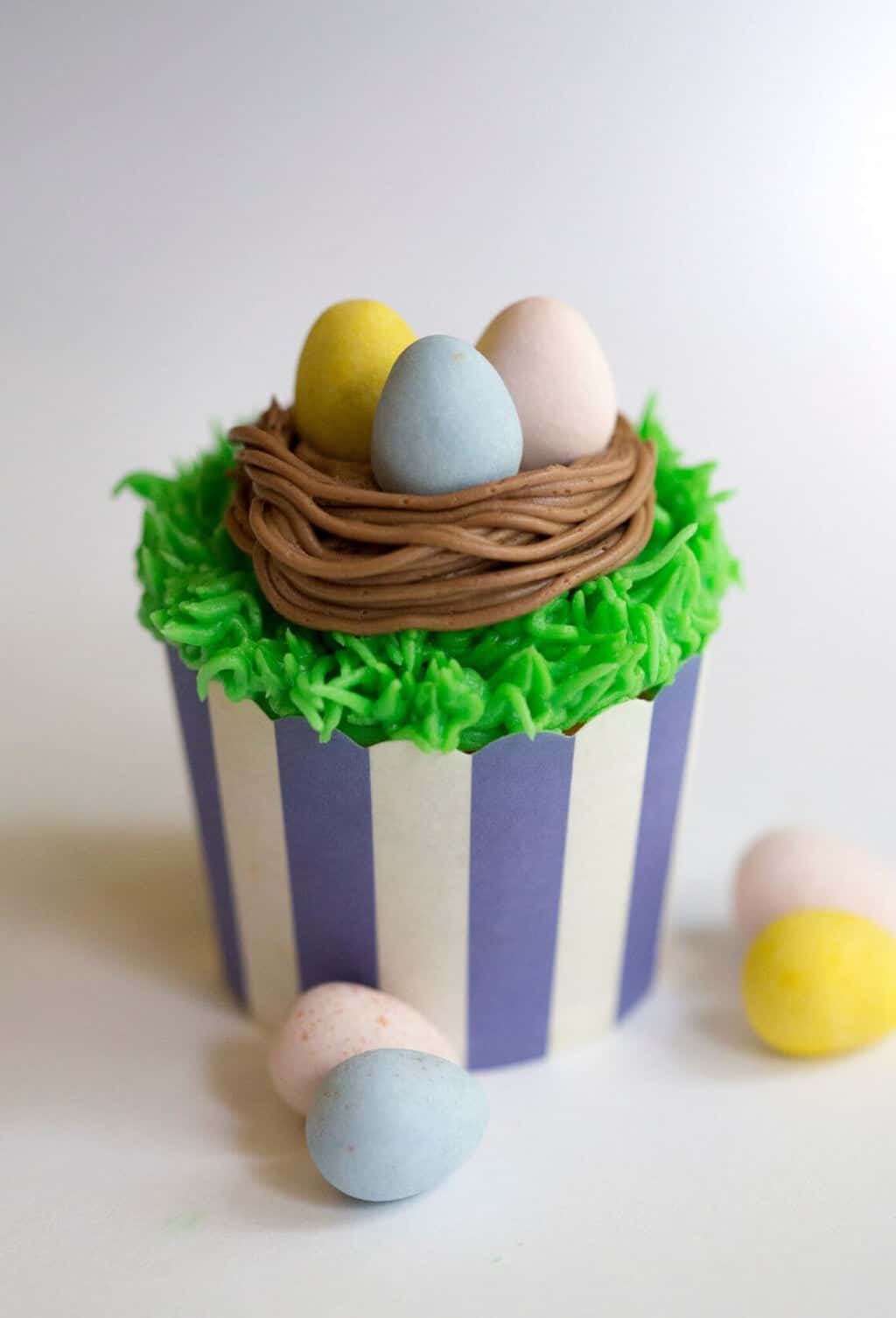 A photo of an Easter cupcake with chocolate eggs in a bird's nest.