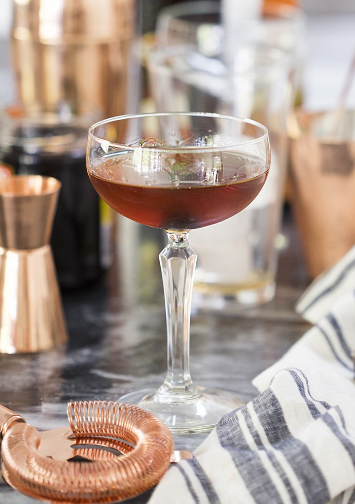 A photo of a manhattan cocktail in a coupe glass among copper bar tools.