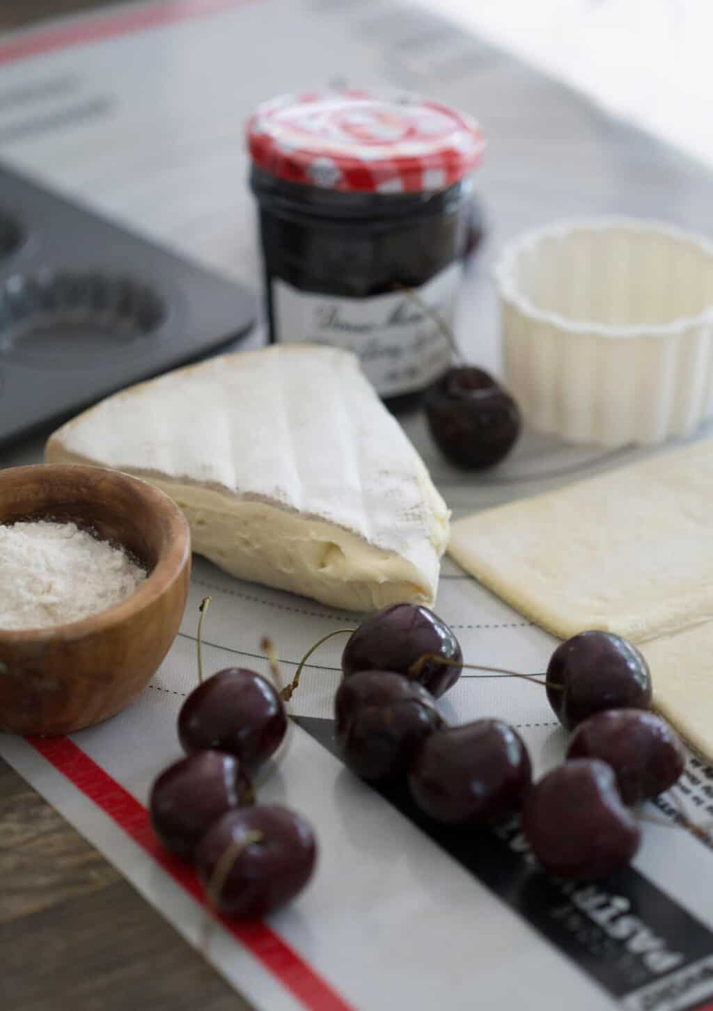 A photo of the ingredients to make brie and cherry bites.
