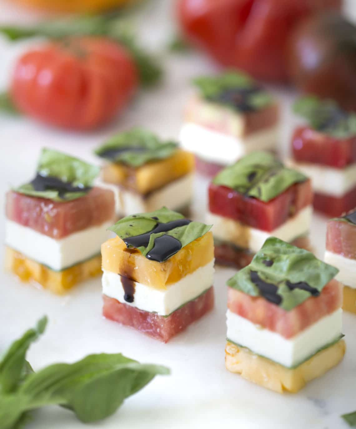 A fancy version of a caprese salad stacked and cut into cubes.