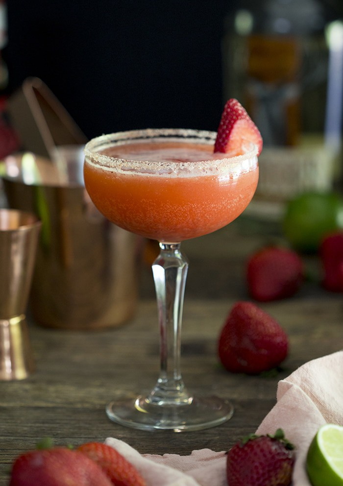 A photo of a strawberry margarita in a coupe glass on a wooden table.